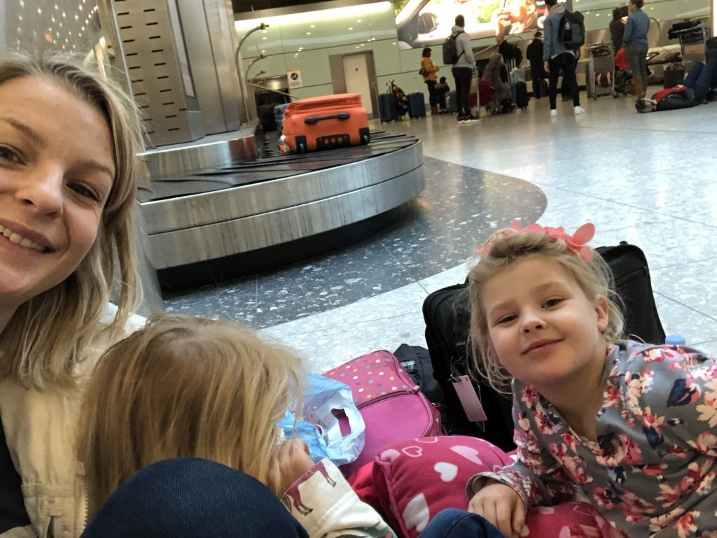 tired children and mum at the baggage carousel. Tips for flying with a baby