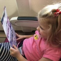 flying with a toddler tips #familytravel child reading airline safety card