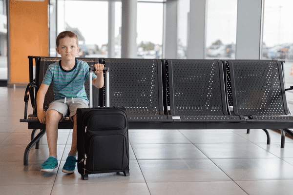 A young boy sitting in an airport waiting room with his luggage.