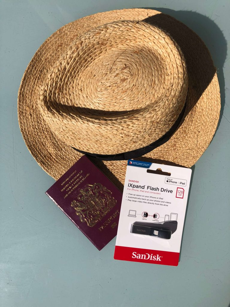 Travel Must Have's: Travel Tech Gadgets for Family Travel:  SanDisk iXpand flash drive with a summer hat and passport
