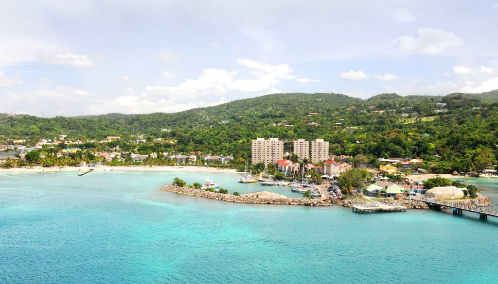 Things to do in Kingston Jamaica with Kids inlcude Ocho Rios, buildings, and blue sea, green mountains.