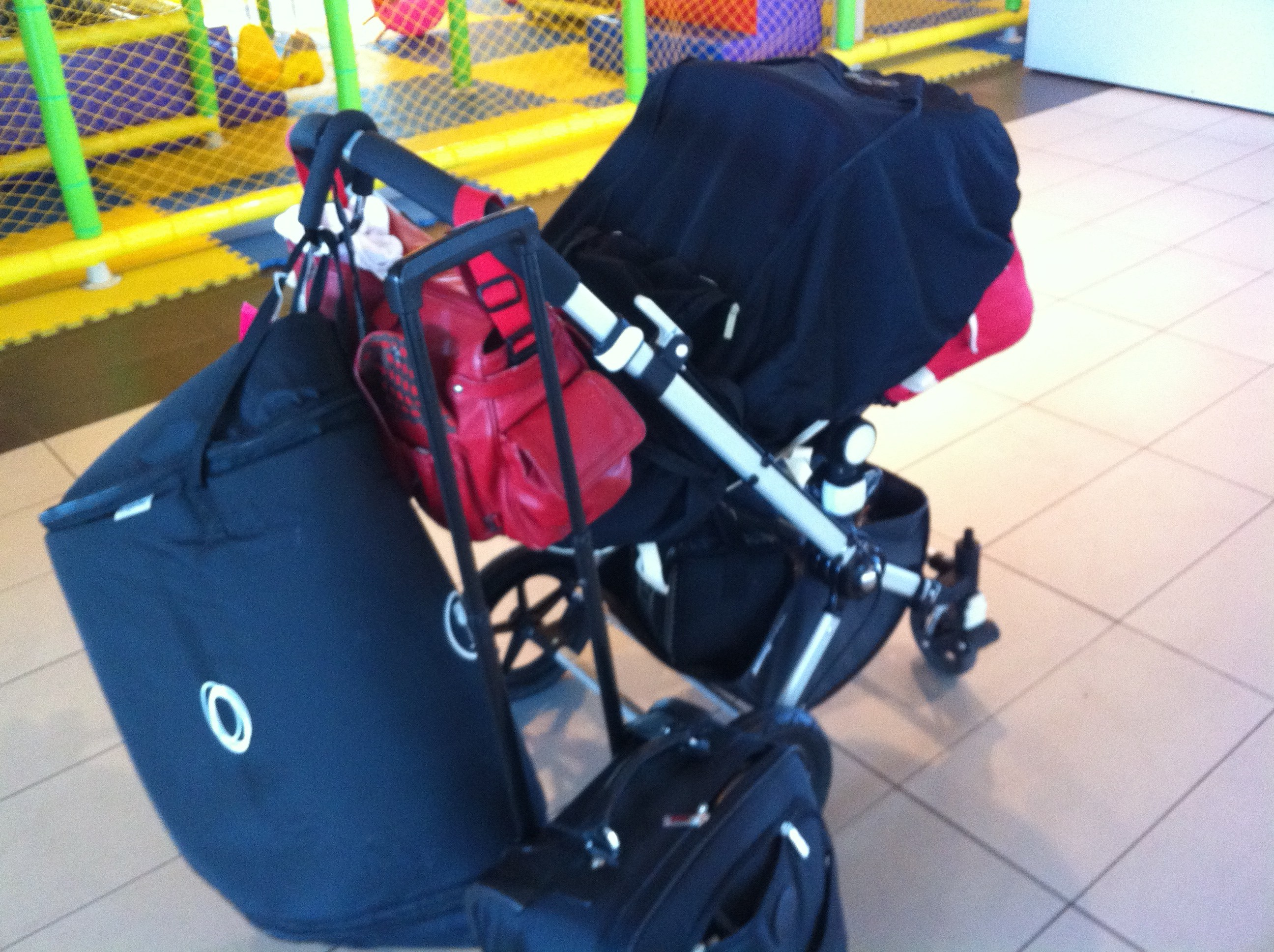 hand luggage and stroller at the airport with stroller travel bag abnd snoozeshade sleep cover over it.