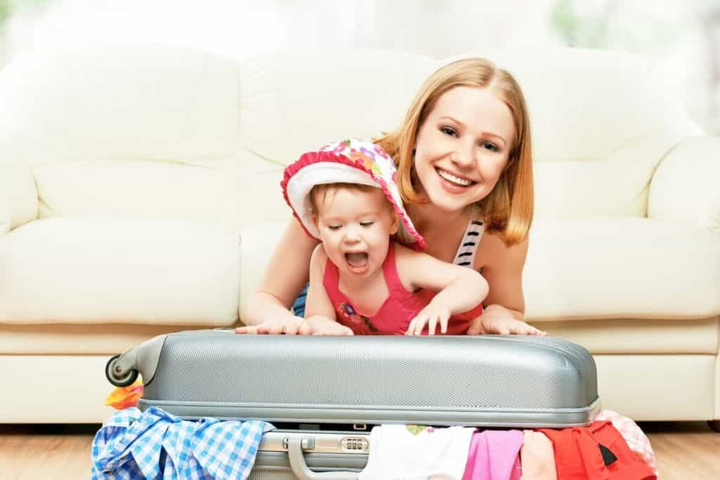 mum with her baby by the suitcase packing their baby travel essentials