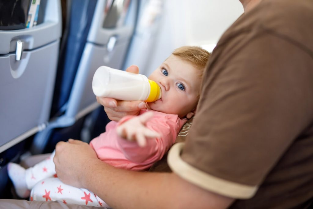 A parent feeding a baby formula on a plane.
