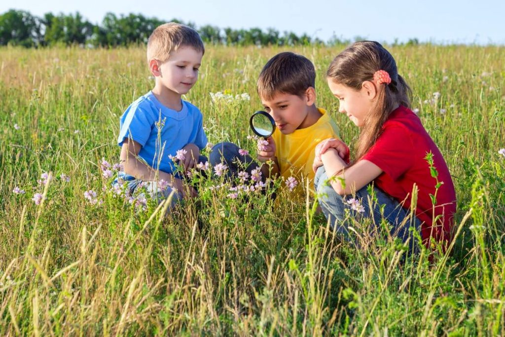 kids with a magnifying glass on nature scavenger hunt
