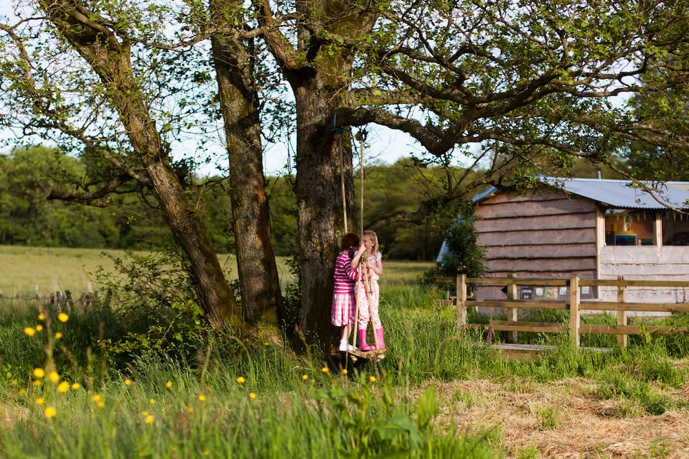 Kids playing on a swing at near a Cosy Under Canvas Glamping Kitchen, Wales