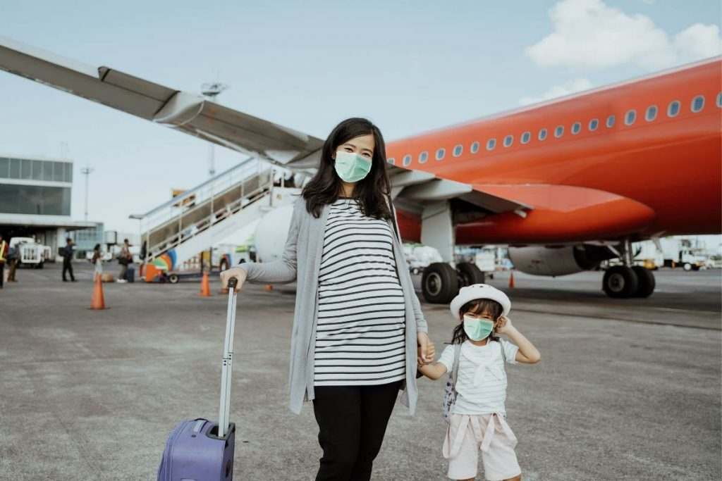pregnant mother and child wearing facemask next to a plane