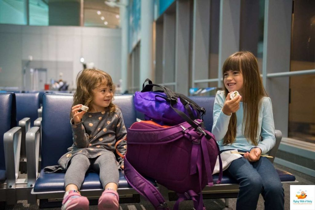 girls at an airport sitting and eating before they travel.